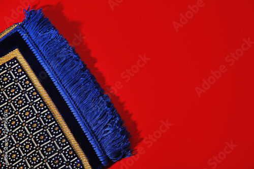 Muslim prayer rug and space for text on color background, top view