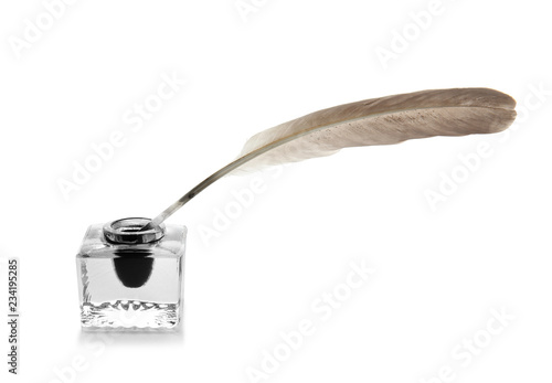 Feather pen and inkwell on white background