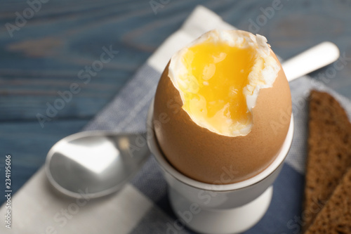Holder with soft boiled egg on table, closeup. Space for text
