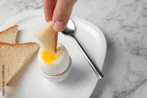 Woman dipping bread into soft boiled egg on table, closeup. Space for text