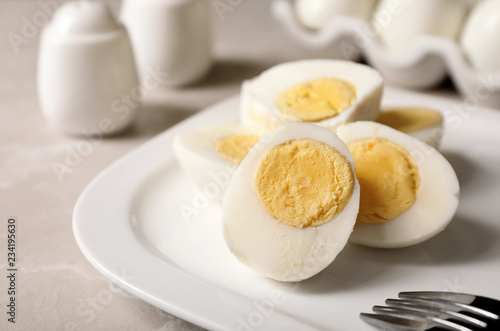 Plate with hard boiled eggs on table