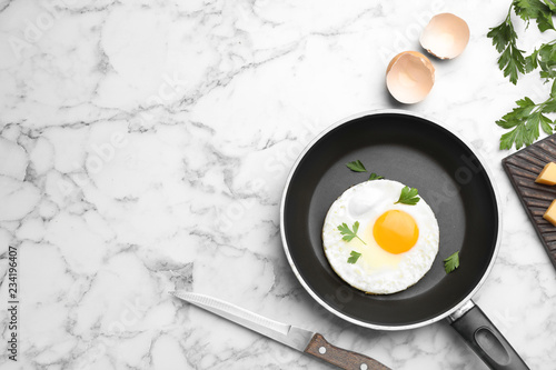 Pan with fried sunny side up egg served on table, flat lay with space for text