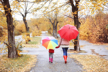 Mother And Daughter With Umbrellas Taking Walk In Autumn Park On Rainy Day
