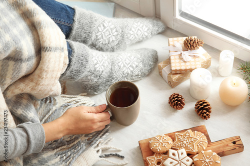 Woman relaxing with cup of hot winter drink near window. Cozy season