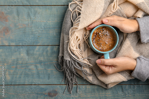 Obraz Woman with warm scarf holding cup of hot winter drink on wooden background, top view. Space for text - fototapety do salonu