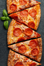 Tasty Pepperoni Pizza And Cooking Ingredients Tomatoes Basil On Black Concrete Background. Top View Of Hot Pepperoni Pizza. Flat Lay