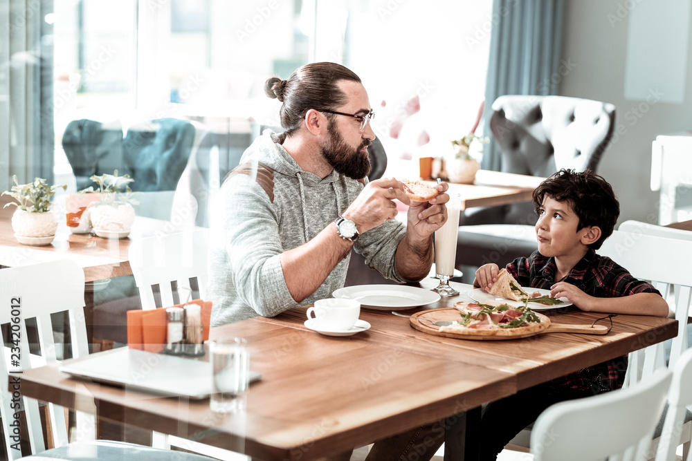 Fototapety, obrazy: Lovely son. Beaming bearded man wearing glasses looking at his lovely son while eating pizza for lunch