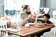 Lovely son. Beaming bearded man wearing glasses looking at his lovely son while eating pizza for lunch