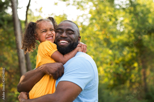 Father laughing and playing with his daugher.