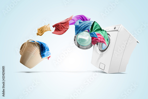 Photo Clothing from laundry basket go into the washing machine