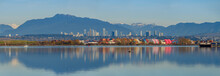 Panoramic View Of Cargoes At Dock With Colourful Reflection On The River And City Skyline And Mountains At Background At Richmond, BC