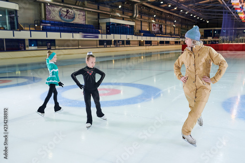 Full  length portrait of female coach  training  little girls figure skating in indoor rink, copy space