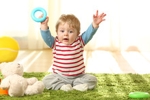 Happy Baby Raising Arms With A Toy On The Floor