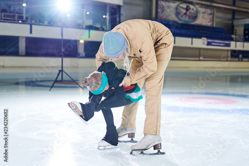 Full length portrait of female coach helping little girl doing figure skating moves in indoor rink, copy space