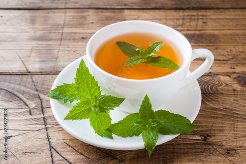 Cup of hot tea with mint and brown sugar on a wooden table