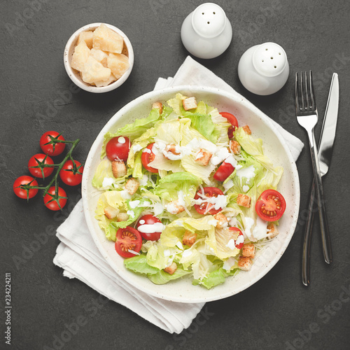 Fotografía  Caesar salad on white plate over black concrete background