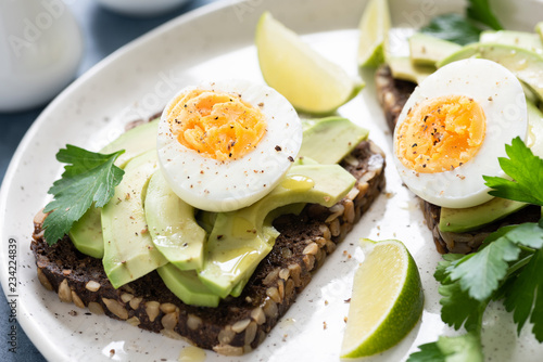 Whole grain rye toast with avocado and egg garnished with parsley. Healthy snack, breakfast or lunch