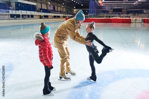 Portrait of two little girls learning to figure skate during training with female coach in indoor rink