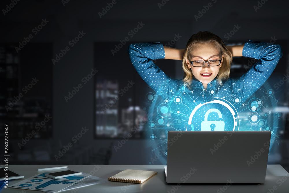 Fototapeta Beautiful blonde in dark office working on laptop and getting net access