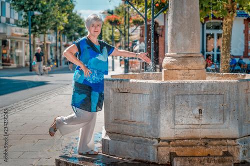 Staande foto India Seniorin am Brunnen