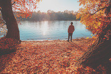 A Man Standing On The River Bank In Autumn And Looking At Water