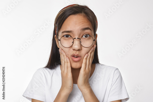 Fototapeta Studio shot of frustrated young Chinese female in round spectacles touching cheeks, having painful facial expression because of toothache. Nerdy Korean girl frowning, holding hands on face obraz na płótnie