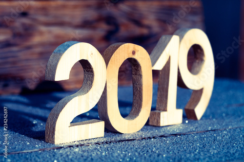Fotografía  Wooden number 2019 on wooden background. Happy new Year 2019.