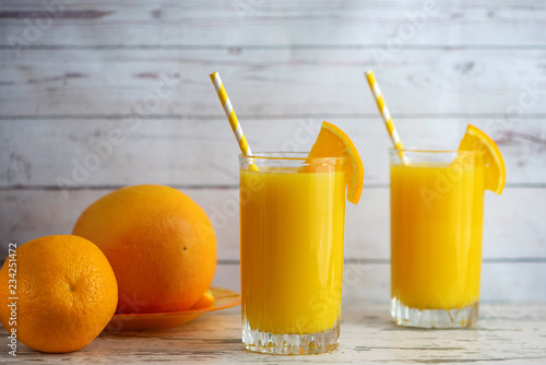Glass of Fresh Orange Juice on light wooden background. Side view