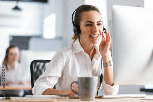 Stampa su Tela Emotional business woman in office callcenter working with computer wearing headphones
