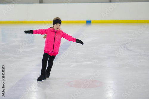 Little girl learning to ice skate. Figure skating school. Young figure skaters practicing at indoor skating rink.