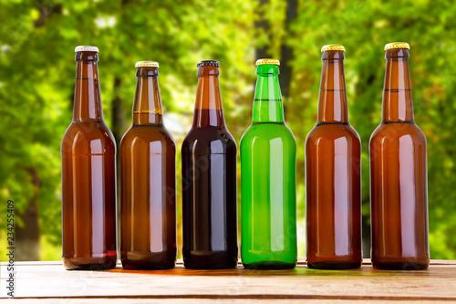 Tuinposter Bier / Cider beer on table on blurred park background, summer drinks,many coloured bottles