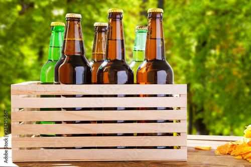 Tuinposter Bier / Cider craft beer on wooden boxon blurred forrest background, summer drinks,coloured bottles