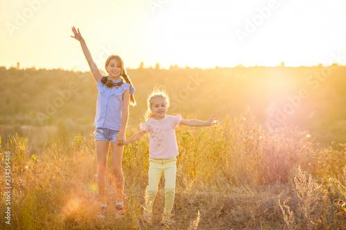 Fototapeta Little smiling girls stand on sunshine evening field with joyfully raised hands obraz na płótnie