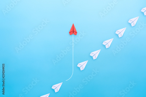 Fotografie, Obraz  Business concept for innovation and solution with group of white paper plane in one direction and one red paper plane pointing in different way on blue background