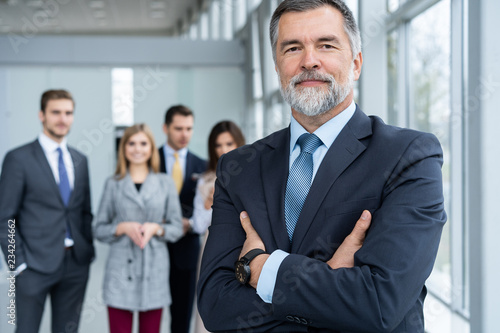 Photo  Businessteam in office, Happy Senior Businessman in His Office is standing in front of their team