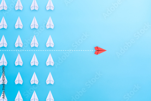 Photo  Business concept for innovation and solution with group of white paper plane in one direction and one red paper plane pointing in different way on blue background