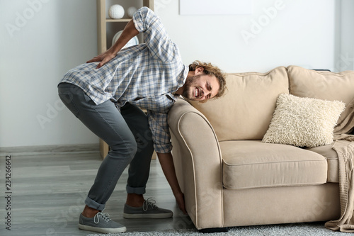 Young man suffering from back pain after carrying heavy furniture Canvas Print