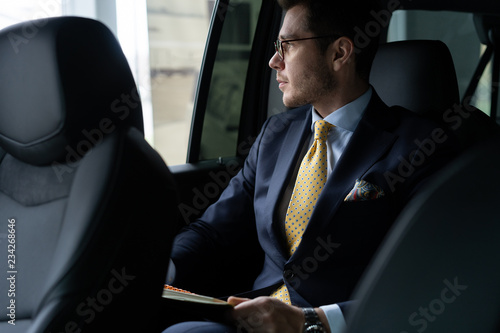 Young businessman sitting on back seat of the car, while his chauffeur is driving automobile Poster Mural XXL