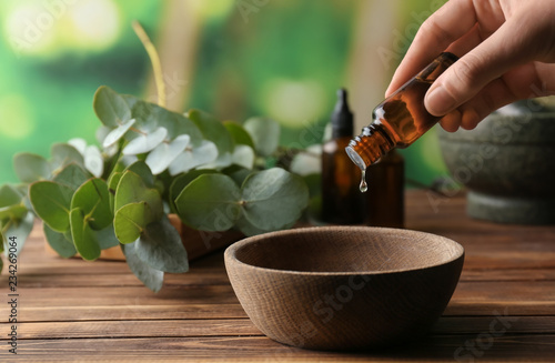 Fototapeta Woman pouring eucalyptus essential oil into bowl on wooden table obraz