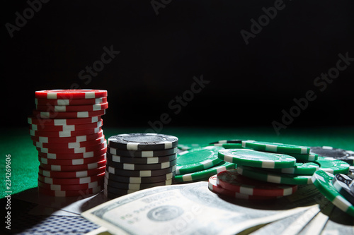 Foto  A stack of gambling chips, cards one hundred dollar bills on green table