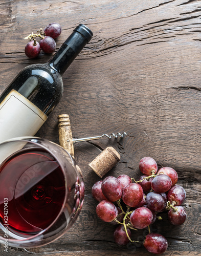 Fotografie, Obraz  Wine glass, wine bottle and grapes on wooden background
