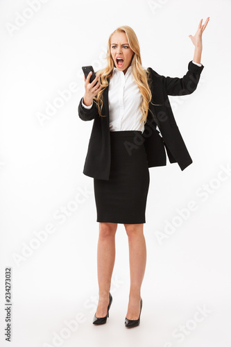 Full length photo of displeased businesswoman wearing office suit screaming on smartphone, isolated over white background in studio