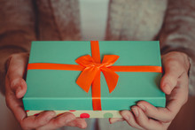 Young Woman Holds A Gift Box With A Bow Close Up