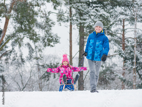 Christmas Vacation Sled.Happy Boy And Girl Riding Sled And Having Fun Children Play