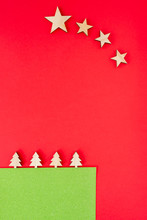 Alternative Christmas Card Made Of Wooden Trees And Stars On A Red Background