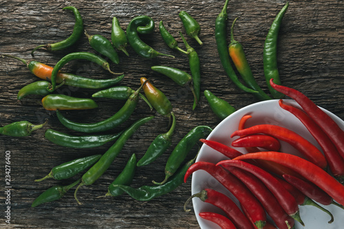 Tuinposter Kruiderij peper on plate/ Red and green hot peppers on an old wooden board and white plate