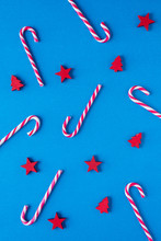 Above View Of A Christmas Red And White Candy Canes, Wooden Trees And Stars Decoration On Blue Background