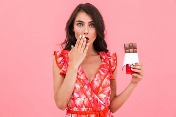 Shocked pretty young woman posing isolated over pink background wall holding chocolate.