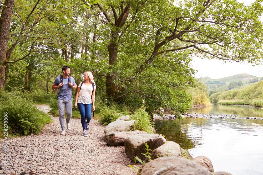 Fototapeta Couple Hiking Along Path By River In UK Lake District