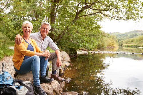 Photographie  Portrait Of Senior Couple On Hike Sitting By River In UK Lake District